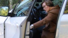 Una mujer consigue en un coche blanco y cierra la puerta metrajes