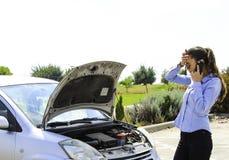 Una mujer consigue pegada con un coche quebrado, ayuda de las necesidades, el coche no motiva Fotografía de archivo libre de regalías