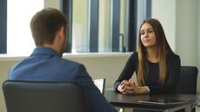 Una mujer contesta a las cuestiones del patrón en la entrevista almacen de metraje de vídeo