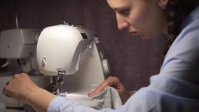 Una mujer cose la ropa en una máquina de coser por la luz de una lámpara Moda, creación y adaptación almacen de metraje de vídeo