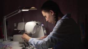 Una mujer cose la ropa en una máquina de coser por la luz de una lámpara Moda, creación y adaptación metrajes