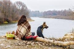 Una mujer cubierta con la tela escocesa caliente está sentando la parte trasera en el río del banco del tha con un perro por su l imagen de archivo
