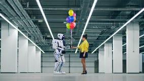 Una mujer da el manojo de globos a un droid blanco almacen de video