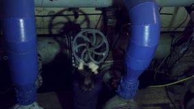 Una mujer da vuelta a la válvula industrial almacen de metraje de vídeo