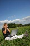 Una mujer dada una sacudida eléctrica con una computadora portátil Imágenes de archivo libres de regalías