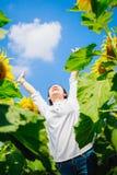 Una mujer de Asia, muchacha feliz en campo del girasol por la mañana Imagen de archivo libre de regalías