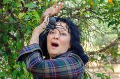 Una mujer de griterío en un ataque de pánico del arachnophobia imagen de archivo