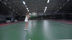 Una mujer de los deportes en la ropa blanca sirve una alimentación de la bola con la rejilla mientras que juega a tenis en el gim metrajes