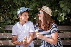 Una mujer de mediana edad atractiva con su hijo adolescente que se sienta encendido Foto de archivo