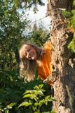 Una mujer de mediana edad blanca de risa mira a escondidas hacia fuera de detrás un árbol en el bosque imagenes de archivo