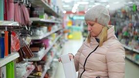 Una mujer de mediana edad en un sombrero y abajo una chaqueta elige un termo negro en un supermercado almacen de metraje de vídeo