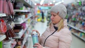 Una mujer de mediana edad en un sombrero y abajo una chaqueta elige un termo en un supermercado almacen de video