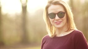 Una mujer de mediana edad linda mira en la cámara estrictamente y benévolo sonriendo Ella lleva las gafas de sol Una muchacha des almacen de video