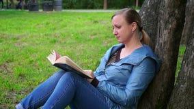 Una mujer de mediana edad que se sienta en la hierba cerca de un árbol y que lee un libro metrajes