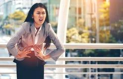 Una mujer de negocios asiática tiene dolor abdominal severo durante trabajo foto de archivo libre de regalías