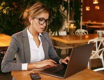 Una mujer de negocios atractiva joven que se sienta en un café con un lapto Foto de archivo libre de regalías
