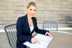 Una mujer de negocios bonita que hace una entrada en su calendario Imagenes de archivo