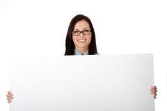 Una mujer de negocios bonita que lleva a cabo una muestra en blanco Imagen de archivo libre de regalías