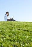 Una mujer de negocios en una computadora portátil en un campo Foto de archivo libre de regalías