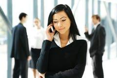 Una mujer de negocios joven que habla en el teléfono Imágenes de archivo libres de regalías