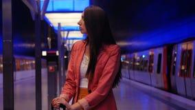 Una mujer de negocios moderna que espera su tren metrajes