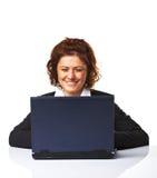 Una mujer de negocios que sonríe mientras que trabaja en la computadora portátil Imagen de archivo