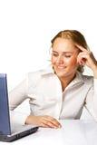 Una mujer de negocios que sonríe mientras que trabaja en la computadora portátil Fotos de archivo libres de regalías