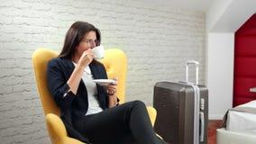 Una mujer de negocios relajada y sonriente tomando café disfrutando de un descanso durante un viaje de negocios de mediano alcanc almacen de video