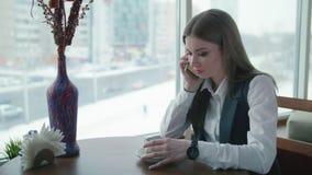 Una mujer de negocios se está sentando en un café y está sonriendo y está hablando en el teléfono almacen de video