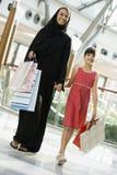 Una mujer de Oriente Medio con compras de la muchacha Imagen de archivo libre de regalías