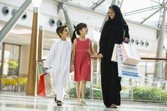 Una mujer de Oriente Medio con dos niños shoping Imagen de archivo libre de regalías