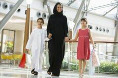 Una mujer de Oriente Medio con hacer compras de dos niños Fotos de archivo libres de regalías