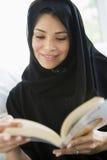 Una mujer de Oriente Medio que lee un libro Imagen de archivo libre de regalías
