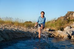 Una mujer de pelo oscuro alegre en la chaqueta coloreada del hilo y del dril de algodón sonríe, camina a lo largo de la playa y g foto de archivo