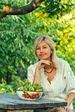Una mujer de pelo rubio con una sonrisa encantadora en la tabla Imagen de archivo