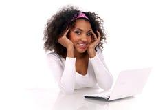 Una mujer de piel morena hermosa con una computadora portátil Imagen de archivo libre de regalías