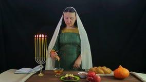 Una mujer de un judío sumerge un pedazo de manzana en la miel e intenta almacen de metraje de vídeo