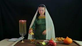 Una mujer de un judío toma un pedazo de una cáliz, sumerge en miel e intenta almacen de video