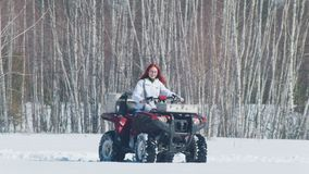 Una mujer del bosque A del invierno con moto de nieve que monta del pelo del jengibre en el tiempo del día almacen de metraje de vídeo