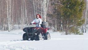 Una mujer del bosque A del invierno con moto de nieve que monta del pelo del jengibre metrajes