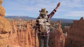 Una mujer del caminante aumenta su mano, colocándose sobre el borde del barranco del bryce almacen de video