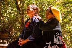 Una mujer del grupo de Wa que hace el masaje para su amigo Foto de archivo