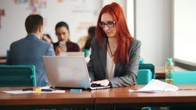 Una mujer del jengibre en los vidrios que se sientan en la oficina y que trabajan por el ordenador portátil Comprobando su teléfo almacen de video