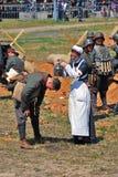 Una mujer del reenactor (enfermera) vierte el agua en la cabeza de un soldado Fotos de archivo