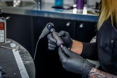 Una mujer del tattooist prepara cuidadosamente su máquina del tatuaje en su estudio imagen de archivo