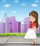 Una mujer delante de los edificios altos que sostienen un artilugio Imágenes de archivo libres de regalías