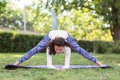 Una mujer delgada en el parque que hace asana hermoso ejercita Yoga practicante de la mujer deportiva en el parque del verano imagenes de archivo