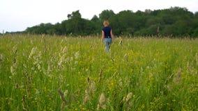 Una mujer delgada en tejanos y una camiseta azul camina lentamente a través del campo entre la hierba alta en la puesta del sol L metrajes