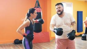 Una mujer delgada y un tonto grueso del hombre y divertirse en gimnasio del boxeo Entrenamiento en guantes de boxeo Taladros de l metrajes