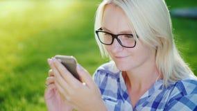 Una mujer descansa en el parque en un día de verano claro, utiliza un smartphone metrajes